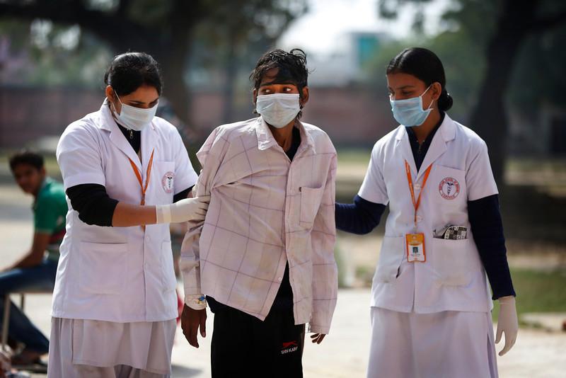 . In this Monday, Feb. 3, 2014 photo, Indian nurses help a tuberculosis patient Manjeet Mishra, 18, center, walk towards his ward at Lal Bahadur Shastri Government Hospital at Ram Nagar in Varanasi, India. (AP Photo/Rajesh Kumar Singh)