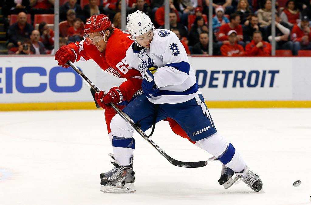 . Detroit Red Wings defenseman Danny DeKeyser (65) defends Tampa Bay Lightning center Tyler Johnson (9) in the first period of an NHL hockey game Saturday, March 28, 2015, in Detroit. (AP Photo/Paul Sancya)