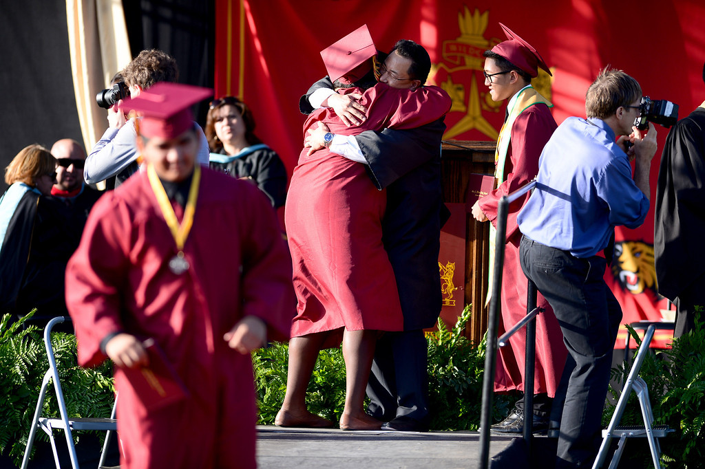 . Patricia Monyei, a district scholar, celebrates after  receiving her diploma by hugging Principal Frank Chang during Wilson High School\'s forty-seventh commencement ceremony Tuesday evening, May 20, 2014 at the Hacienda Heights school. (Photo by Sarah Reingewirtz/Pasadena Star-News)