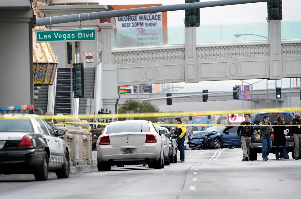 Description of . Las Vegas Metro officers investigate the site of what is being described as a gun battle between shooters in vehicles along the Las Vegas Strip on February 21, 2013 in Las Vegas, Nevada. According to reports gunshots were fired between black SUV at a Maserati, causing the Maserati to crash into a taxi, that burst into flames. Five vehicles were involved in the subsequent crash with the Maserati driver and two people in the taxi being killed.  (Photo by David Becker/Getty Images)