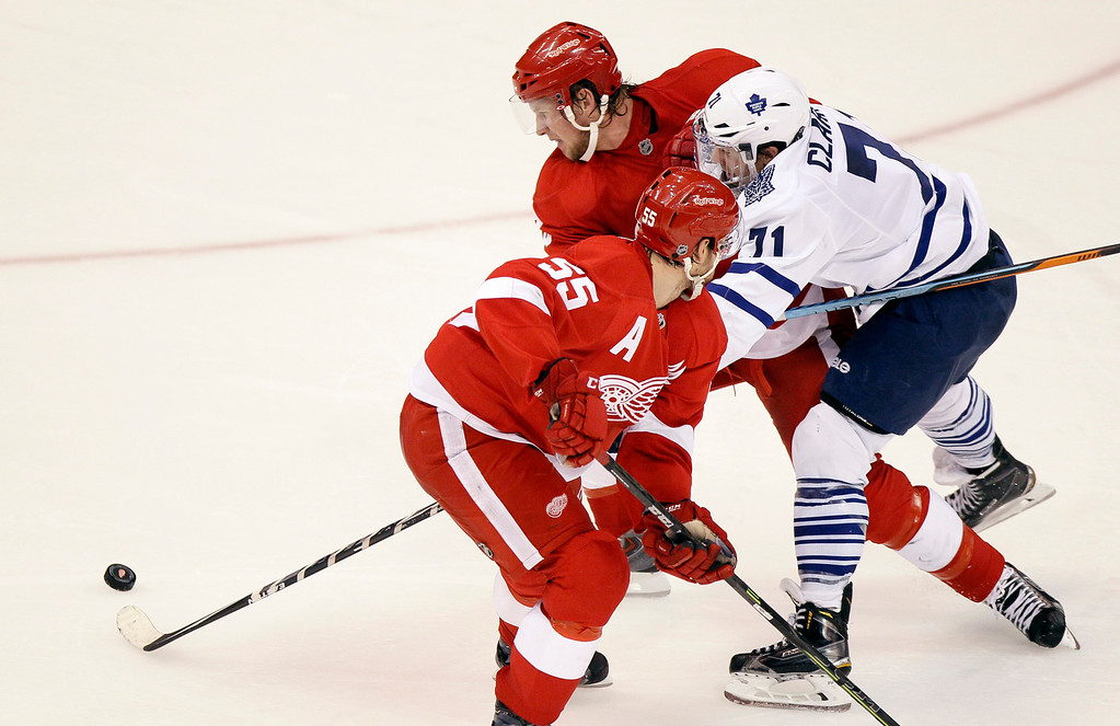 . Toronto Maple Leafs\' David Clarkson (71) is forced off the puck by Detroit Red Wing\'s Justin Abdelkader and Niklas Kronwall (55), of Sweden, during overtime of an NHL hockey game Saturday, Oct. 18, 2014, in Detroit. The Red Wings defeated the Maple Leafs 1-0. (AP Photo/Duane Burleson)