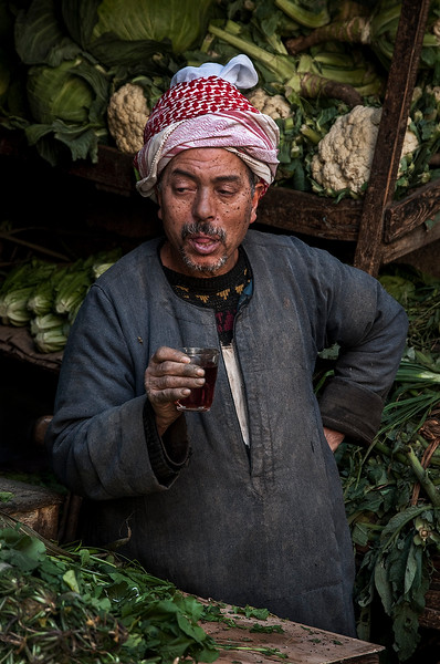 Vegetable vendor taking a tea break at his stall behind the Al-Azhar Mosque.  Cairo, Egypt, 2010.