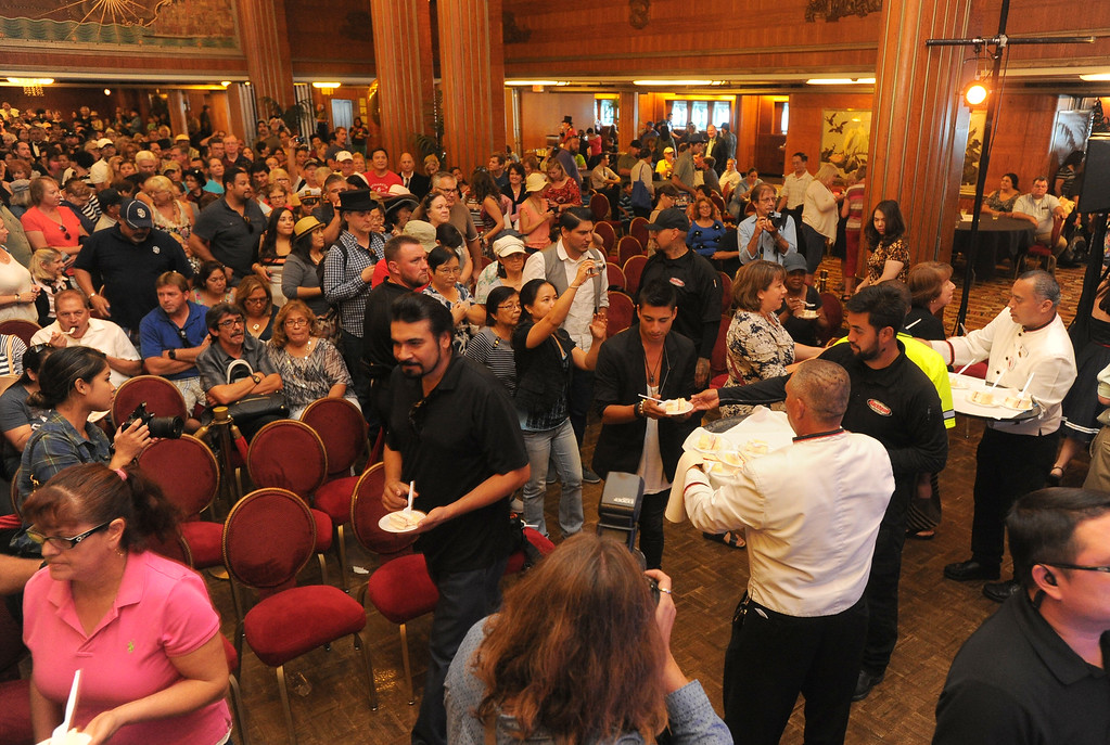 . Guests form a long line in the Grand Salon of the Queen Mary for a slice of cake at the 80th anniversary of her launching in Long Beach, CA on Friday, September 26, 2014. After some speeches and a short film, guests were able to sample a slice of cake from a 15-foot long, 600-pound replica of the ship made by baker Jose Barajas. (Photo by Scott Varley, Daily Breeze)
