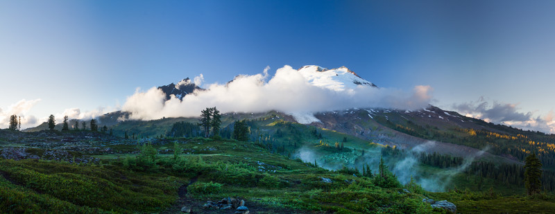 The peak of Mount Baker is seen through a few clouds at sunset in Washington's Cascade Range.
