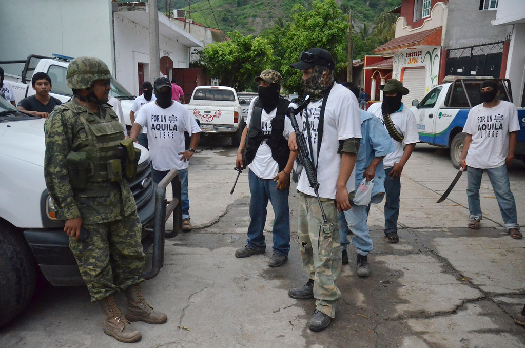 . A Mexican army soldier talks to armed members of a local self-defense group wearing white T-shirts with the slogan \'For a Free Aquila\' in the town of Aquila, Mexico, early Wednesday, July 24, 2013. Mexicoís rough western state of Michoacan, where Aquila is located, is proving just as tough a thorn in the side of President Enrique Pena Nieto as it was for his predecessor after gunmen believed to be working for the Knights Templar cartel launched a coordinated series of a half-dozen ambushes on federal police convoys last Tuesday followed by yet another self-defense group that has sprung up to fight against the Knights Templar.(AP Photo/Gustavo Aguado)