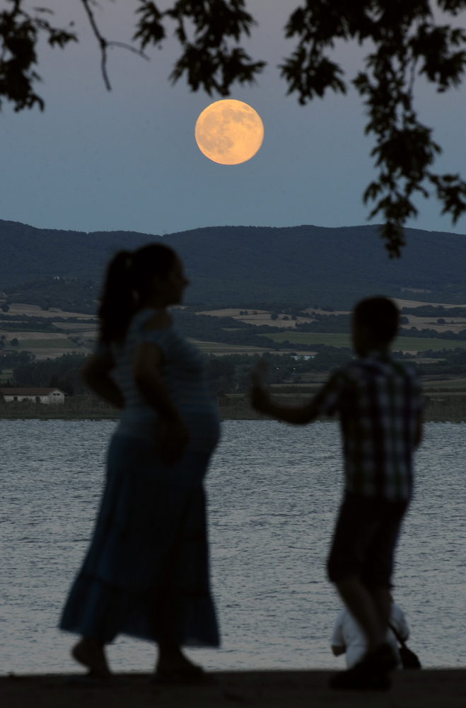 ". A perigee moon also known as a supermoon rises above Dojran Lake in southeastern Macedonia, on Saturday, July 12, 2014. The phenomenon, which scientists call a ""perigee moon,\"" occurs when the moon in its elliptical orbit is relatively close to Earth and seen from the Earth near the horizon, appears larger and brighter than other full moons. (AP Photo/Boris Grdanoski)"