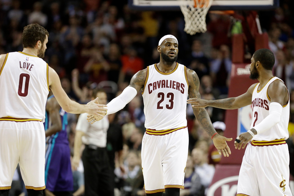 . Cleveland Cavaliers\' LeBron James (23) celebrates a play with Kevin Love (0) and Kyrie Irving in an NBA basketball game against the Charlotte Hornets Monday, Dec. 15, 2014, in Cleveland. (AP Photo/Mark Duncan)