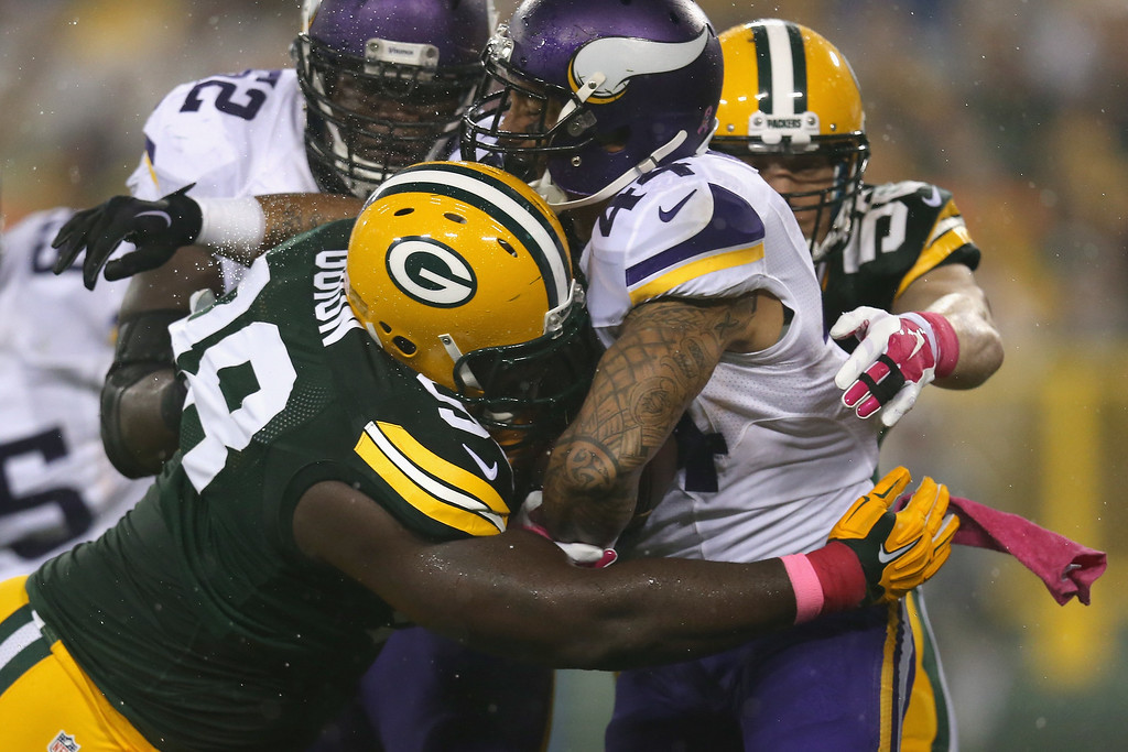 . GREEN BAY, WI - OCTOBER 02:  Matt Asiata #44 of the Minnesota Vikings is tackled by Letroy Guion #98 of the Green Bay Packers at Lambeau Field on October 2, 2014 in Green Bay, Wisconsin.  (Photo by Jonathan Daniel/Getty Images)