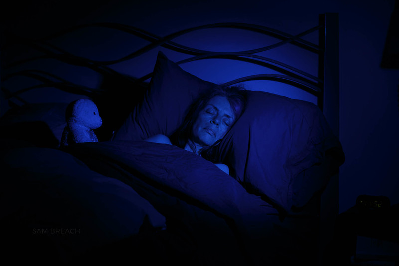 50s woman asleep in bed with teddy bear watching under dark blue light -Night time-photographed by Sam Breach 2020974C1628.jpg