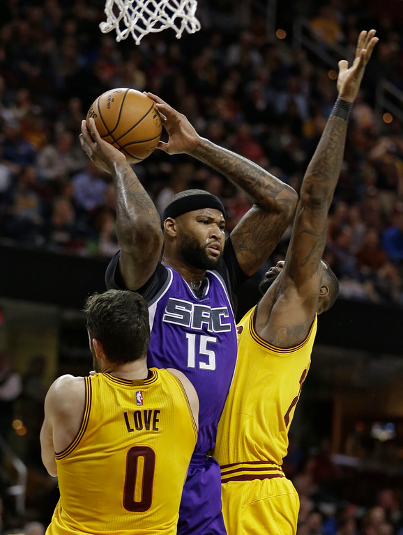 . Sacramento Kings\' DeMarcus Cousins (15) looks to pass against Cleveland Cavaliers\' Kevin Love (0) and LeBron James (23) during the first half of an NBA basketball game, Wednesday, Jan. 25, 2017, in Cleveland. (AP Photo/Tony Dejak)