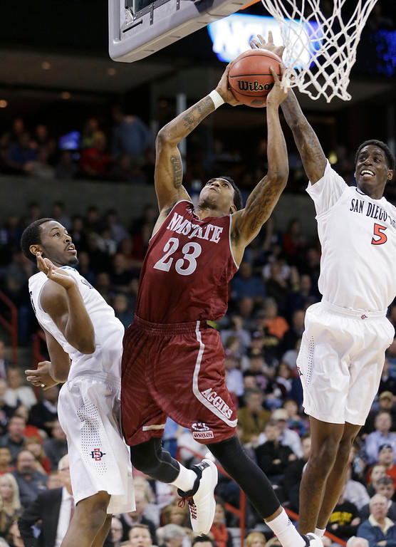 . New Mexico State\'s Daniel Mullings (23) tries to shoot between San Diego State\'s Dwayne Polee II (5) and Xavier Thames in the first half of a second-round game of the NCAA men\'s college basketball tournament in Spokane, Wash., Thursday, March 20, 2014. (AP Photo/Elaine Thompson)