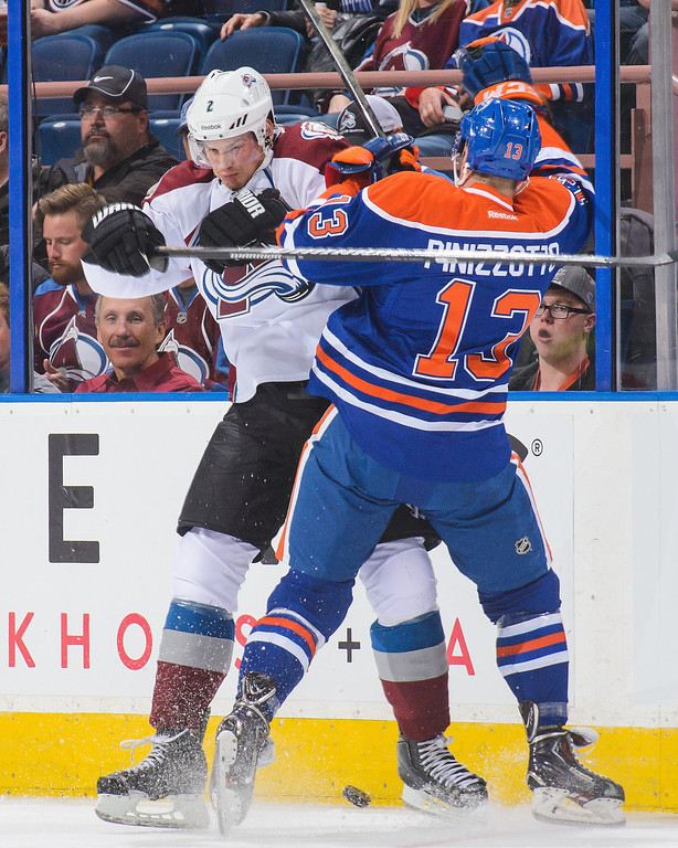 . Steve Pinizzotto #13 of the Edmonton Oilers collides with Nick Holden #2 of the Colorado Avalanche during an NHL game at Rexall Place on April 8, 2014 in Edmonton, Alberta, Canada. (Photo by Derek Leung/Getty Images)