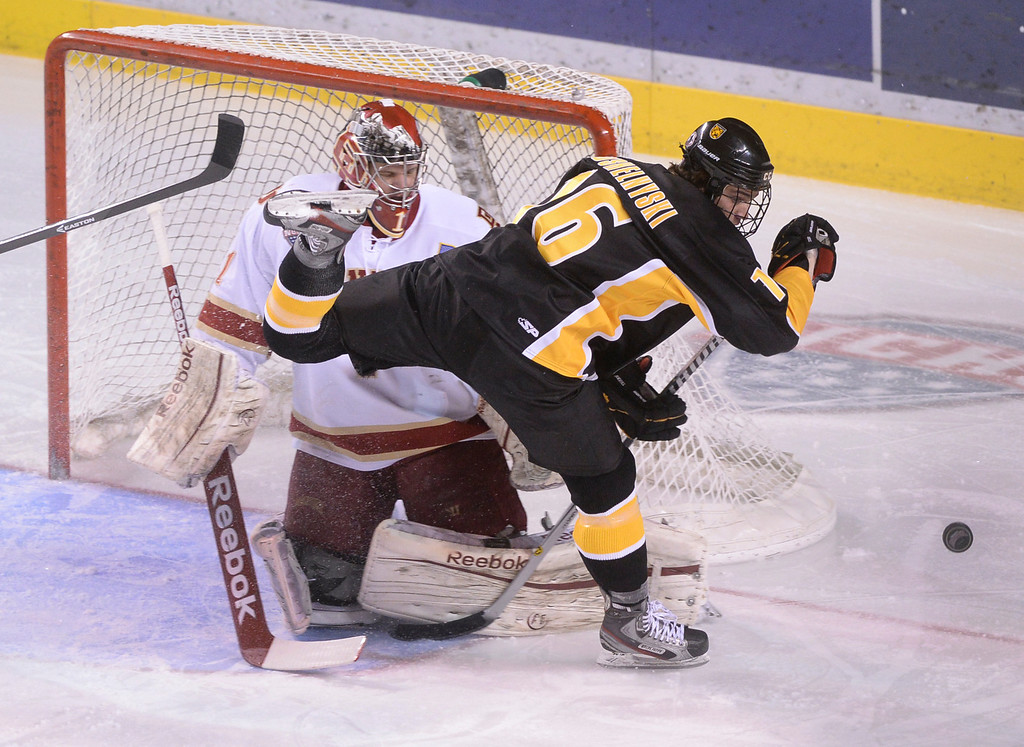 . DENVER, CO. - FEBRUARY 21, 2014: Colorado College wing Alexander Krushelnyski (16) chased the puck in front of Denver goalie Sam Brittain in the first period. The University of Denver hockey team hosted Colorado College at Magness Arena Friday night, February 21, 2014. Photo By Karl Gehring/The Denver Post