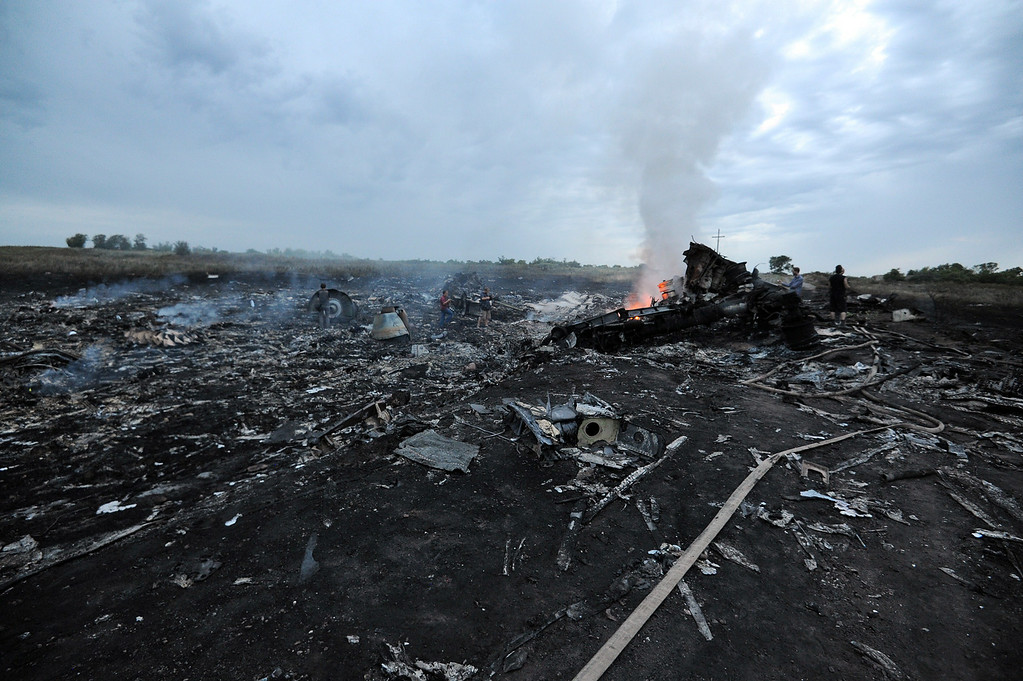 . People stand next to the wreckages of the malaysian airliner carrying 295 people from Amsterdam to Kuala Lumpur after it crashed, near the town of Shaktarsk, in rebel-held east Ukraine, on July 17, 2014. Pro-Russian rebels fighting central Kiev authorities claimed on Thursday that the Malaysian airline that crashed in Ukraine had been shot down by a Ukrainian jet. The head of Ukraine\'s air traffic control agency said Thursday that the crew of the Malaysia Airlines jet that crashed in the separatist east had reported no problems during flight. AFP PHOTO/DOMINIQUE FAGET/AFP/Getty Images