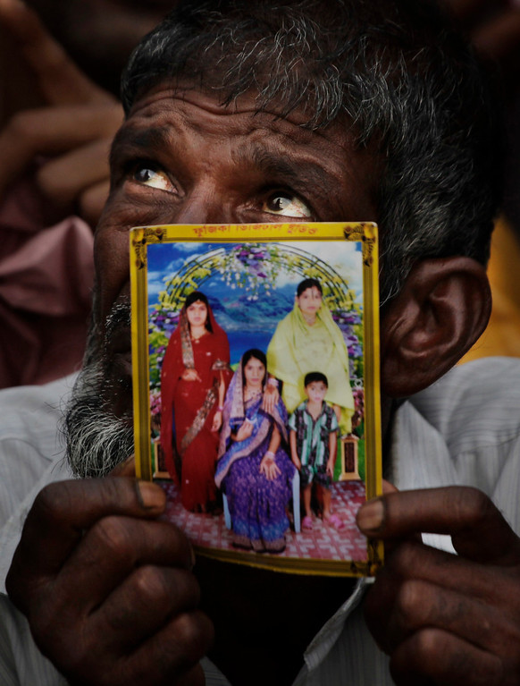 . A Bangladeshi man holds a picture of a relative missing in a building that collapsed Wednesday hold pictures of loved ones at a makeshift morgue in a schoolyard in Savar, near Dhaka, Bangladesh, Saturday, April 27, 2013. Police in Bangladesh arrested two owners of a garment factory in a shoddily-constructed building that collapsed this week, killing at least 324 people, as protests spread to a second city Saturday with hundreds of people throwing stones and setting fire to vehicles. (AP Photo/Kevin Frayer)