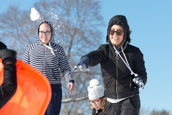 03/04/19 Wesley Bunnell | Staff Ligia Revalos throws a snowball at a friend during a group outing of sledding at Walnut Hill Park on Monday afternoon.