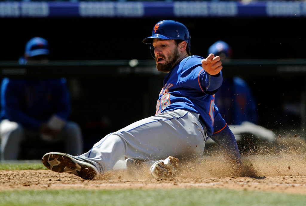 . New York Mets\' Daniel Murphy slides into home plate to score a run during the sixth inning of a baseball game against the Colorado Rockies on Thursday, April 18, 2013, in Denver. (AP Photo/Jack Dempsey)
