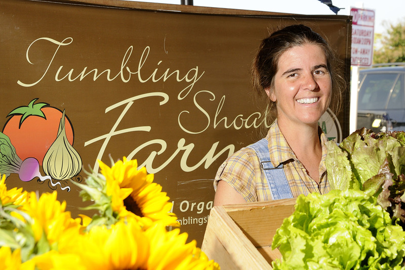 Shiloh Avery, owner of Tumbling Shoals Farm, smiles from behind a bevy of flowers and produce at the Hickory Farmers' Market at the Sails on the Square in downtown Hickory, NC on Saturday, June 14, 2014. Copyright 2014 Jason Barnette