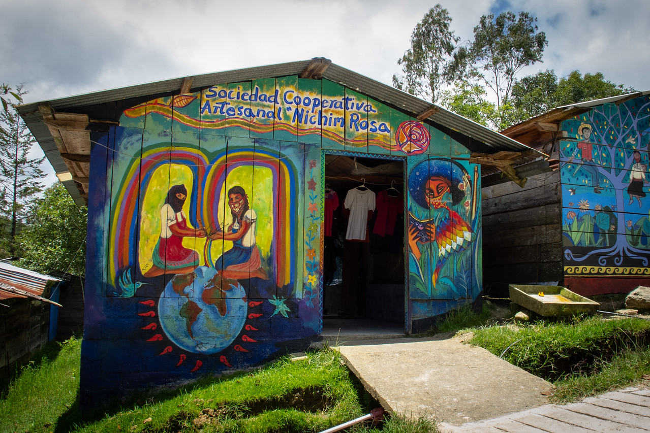 A Small Shop in Oventic With a Zapatista Art Mural on Front Showing Women Weaving a Rainbow
