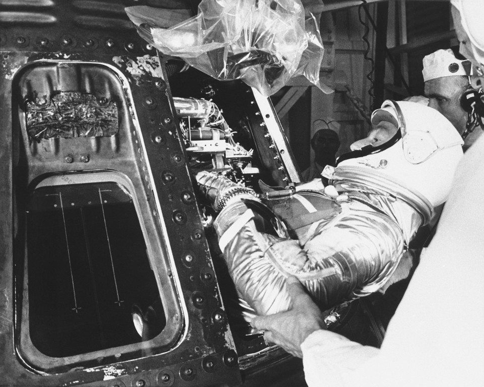 . Astronaut Scott Carpenter slips into the Aurora 7 before being blasted into orbit from Cape Canaveral Florida, May 24, 1962. At right is John Glenn, first American into orbit. (AP Photo)