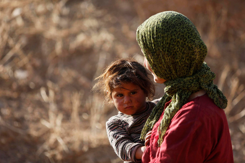 . A Bedouin woman carries her child as she prepares to leave her home in the West Bank village of Wadi al-Maleh, near the border with Jordan April 29, 2013. Israeli soldiers on Monday evicted several hundred Bedouins from the village in the occupied West Bank after the army declared the area a live-fire training zone. The residents of Wadi al-Maleh, a village mostly inhabited by shepherds in the arid area, had almost all left their homes by an evening curfew and retreated to neighboring villages, a local leader told Reuters. REUTERS/Mohamad Torokman