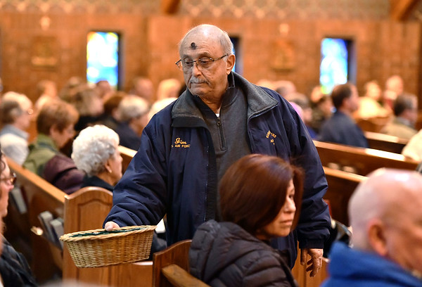 2/26/2020 Mike Orazzi | StaffrJim Bousquet passes the basket during Ash Wednesday services at St. Matthew Church in Forestville on Wednesday. r