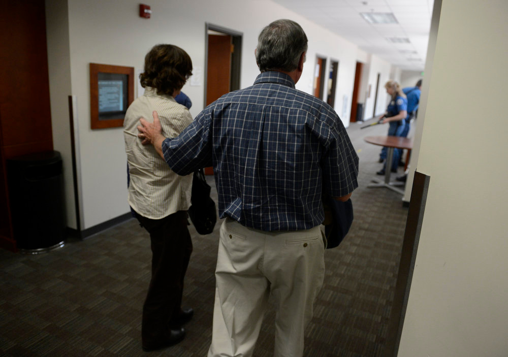 Description of . Parents Arlene and Robert Holmes, of Aurora theater shooting suspect James Holmes, head back into courtroom, Monday April 01, 2013. Earlier that day they learned  prosecution will go for the death penalty in their son case. (Photo By RJ Sangosti/The Denver Post)