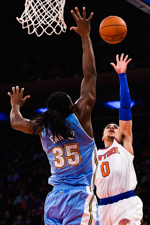 . NEW YORK, NY - NOVEMBER 16: Shane Larkin #0 of the New York Knicks shoots over Kenneth Faried #35 of the Denver Nuggets in the second half at Madison Square Garden on November 16, 2014 in New York City. NOTE TO USER: User expressly acknowledges and agrees that, by downloading and/or using this photograph, user is consenting to the terms and conditions of the Getty Images License Agreement.  (Photo by Alex Goodlett/Getty Images)
