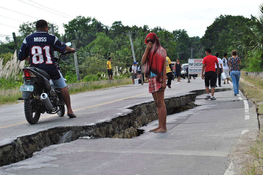 . Residents walk along a damaged road following a 7.2-magnitude earthquake that hit Bohol, central Philippines, Tuesday, Oct. 15, 2013.  (AP Photo)