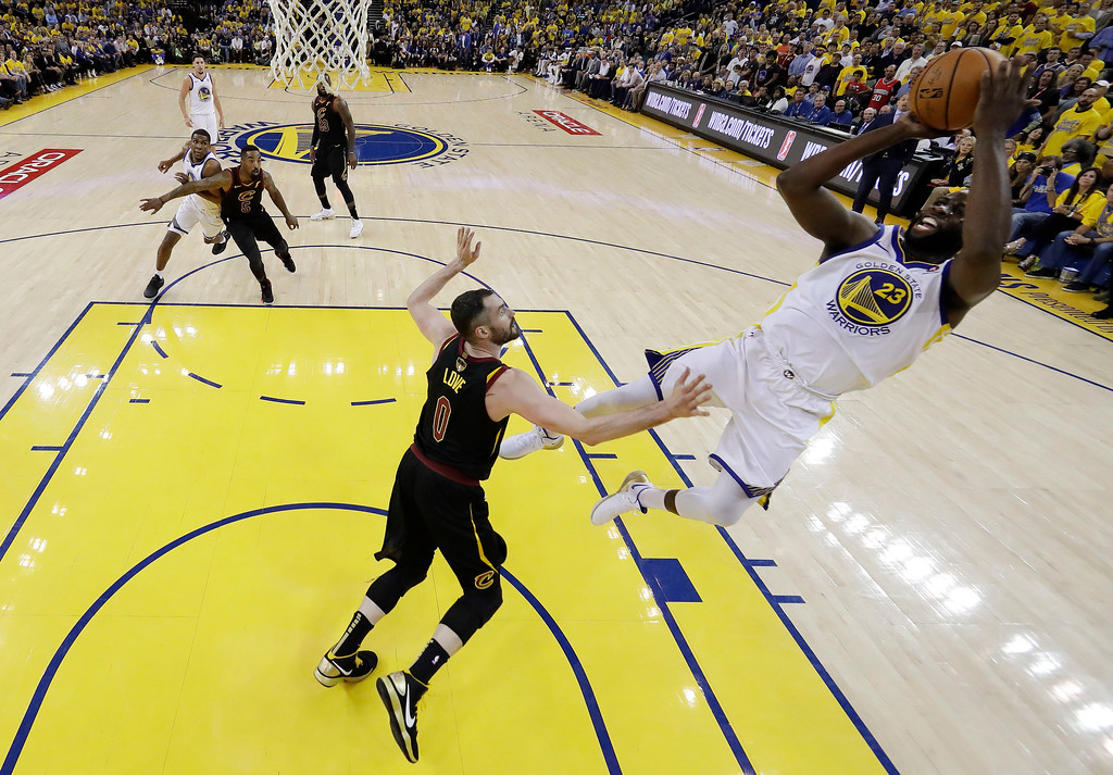. Golden State Warriors\' Draymond Green, right, shoots over Cleveland Cavaliers\' Kevin Love (0) during the second half of Game 1 of basketball\'s NBA Finals Thursday, May 31, 2018, in Oakland, Calif. (AP Photo/Marcio Jose Sanchez)
