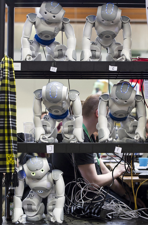 . MAGDEBURG, GERMANY - APRIL 26:  Robots stand at a shelf near the play field at the 2013 RoboCup German Open tournament on April 26, 2013 in Magdeburg, Germany. The robots, which are a model called Nao, manufactured by Aldebaran Robotics, perform autonomously and communicate with one another via WLAN. The three-day tournament is hosting 43 international teams and 158 German junior teams that compete in a variety of disciplines, including soccer, rescue and dance.  (Photo by Jens Schlueter/Getty Images)