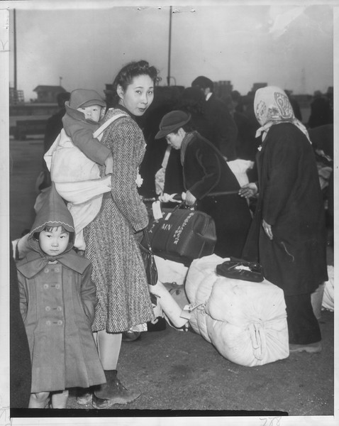 """""""Reluctant -- Abo Sadako carries baby, 10 months old, on back as she prepares to leave for Japan.  She didn't want to leave.""""--caption on photograph"""