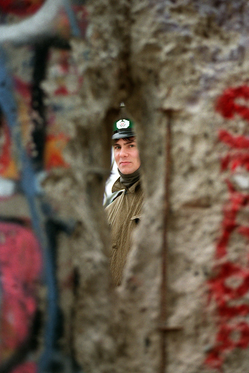 . An East German policeman (Vopo) looks through a hole made in the Berlin Wall next to the Brandebourg Gate, on November 21, 1989.       (Photo credit GERARD MALIE/AFP/Getty Images)