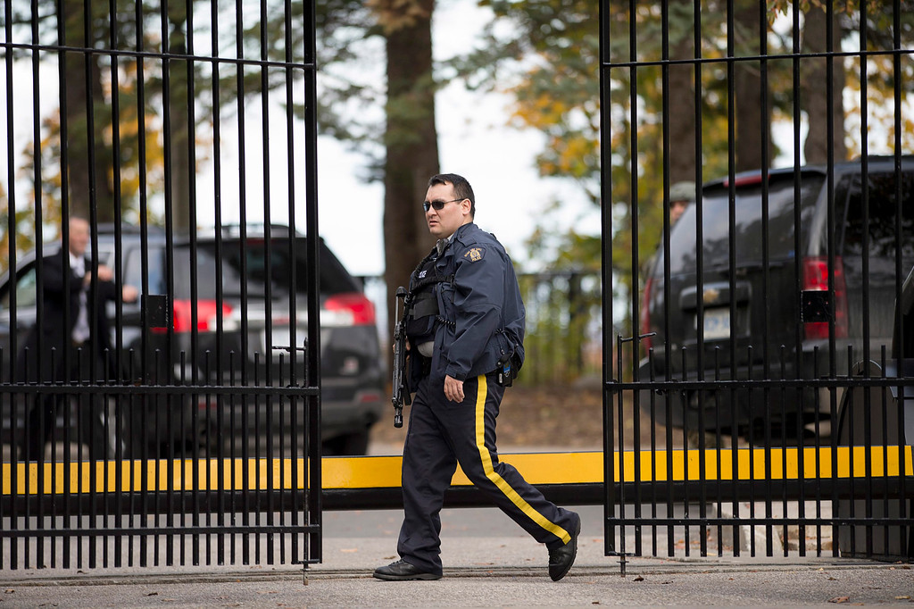 . An armed RCMP officer stands guard at 24 Sussex Dr., the official residence of the Prime Minister, on Wednesday, Oct. 22, 2014.  A soldier standing guard at the National War Memorial has been shot by an unknown gunman and there have been reports of gunfire inside the halls of Parliament. (AP Photo/The Canadian Press, Justin Tang)