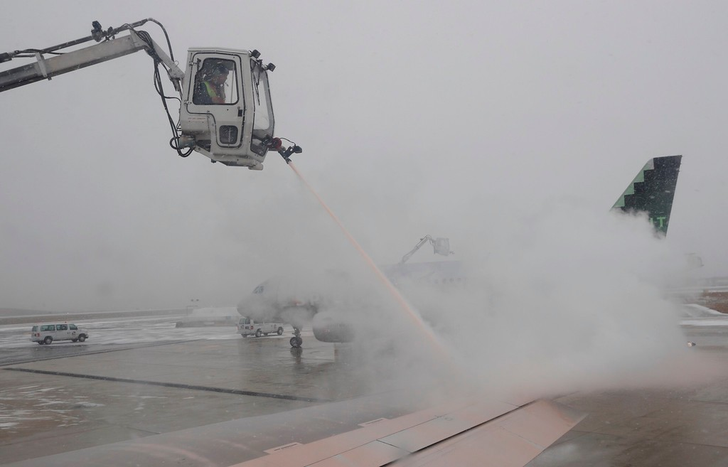 . As snow falls, workers de-ice the wing of a Delta aircraft after de-icing the Spirit aircraft in the background on the tarmac at Baltimore-Washington International Airport, in Baltimore, Md., Saturday, Jan. 7, 2017. Winter storms along the east coast have caused flight delays. (AP Photo/Carolyn Kaster)
