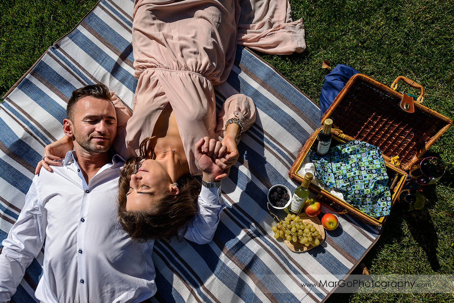 man in white shirt and woman in pink dress lying on the blue blanket next to picnic basket during Napa Valley engagement session at Frank Family Vineyards in Calistoga