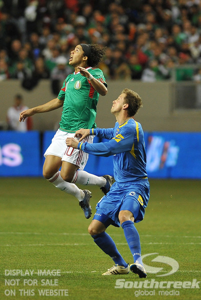 Mexico's Forward Giovani Dos Santos (#10) goes up for a header while Bosnia-Herzegovina's Defender Adnan Mravac (#5) looks on during Soccer action between Bosnia-Herzegovina and Mexico.  Mexico defeated Bosnia-Herzegovina 2-0 in the game at the Georgia Dome in Atlanta, GA.