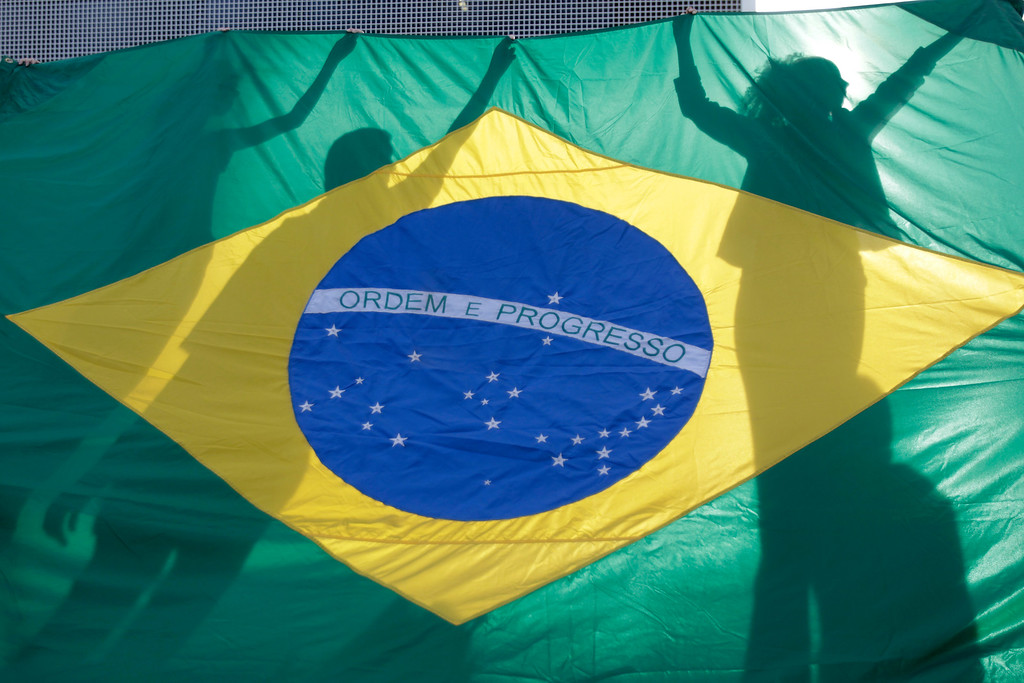 . Demonstrators hold a Brazilian flag during a protest in front of the Brazilian National Congress in Brasilia, Brazil, Monday, June 17, 2013. Protesters massed in at least seven Brazilian cities Monday for another round of demonstrations voicing disgruntlement about life in the country, raising questions about security during big events like the current Confederations Cup and a papal visit next month. (AP Photo/Eraldo Peres)