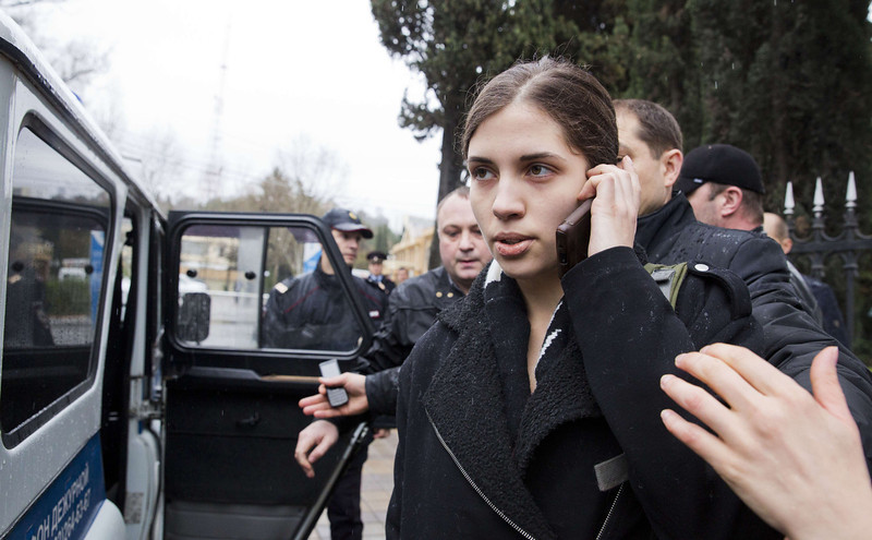 . A members of Russian punk group Pussy Riot, Nadezhda Tolokonnikova, speaks by her cell phone, as she is escorted to a police car after being detained in the Adler district of Sochi, on February 18, 2014. Tolokonnikova and her fellow member of the punk group, Maria Alyokhina, were arrested today in the centre of the Winter Games host city of Sochi over accusations of theft from a local hotel. (EVGENY FELDMAN/AFP/Getty Images)