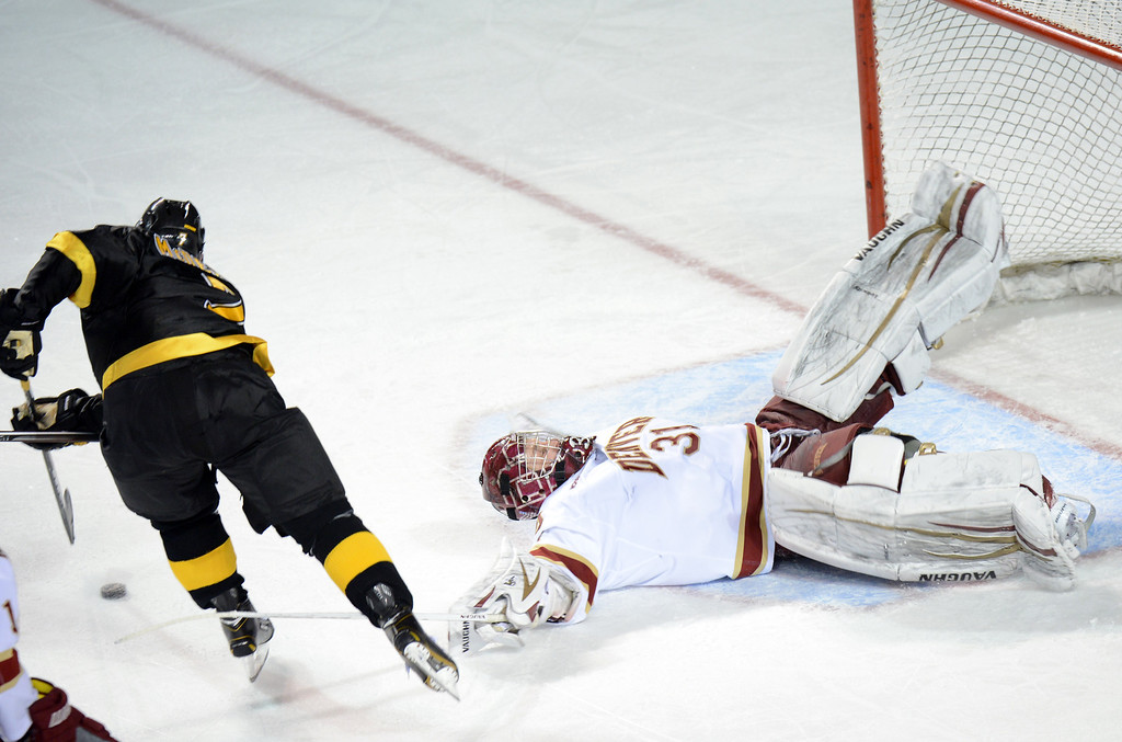 . DENVER, CO. - FEBRUARY 08: Juho Olkinuora of University of Denver #31 saves the goal from the shot of Eamonn McDermott of Colorado College #7  February 8, 2013 at Magness Arena in Denver, Colorado. The game was over 1-1 in OT. (Photo By Hyoung Chang/The Denver Post)