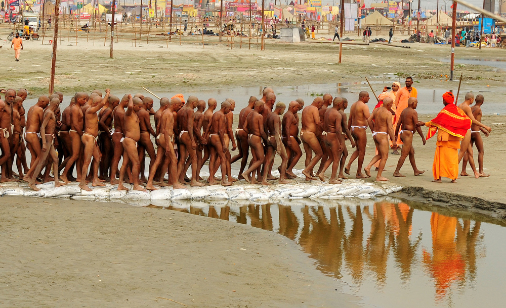 Description of . Newly initiated 'naga sadhus' walk to the river to perform rituals on the banks of the Ganga River during the Maha Kumbh festival in Allahabad on Febraury 6, 2013.   During every Kumbh Mela, the diksha - ritual of initiation by a guru - program for new members takes place.   Sanjay Kanojia/AFP/Getty Images