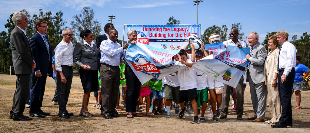 . Kids break through a banner at the renovation kick-off for the John Ferraro Soccer Fields at Griffith Park.  The city plans to work with the LA84 Foundation to help raise the 10 million necessary to renovate the fields and convert them to artificial turf.   ( Photo by David Crane/Los Angeles Daily News )