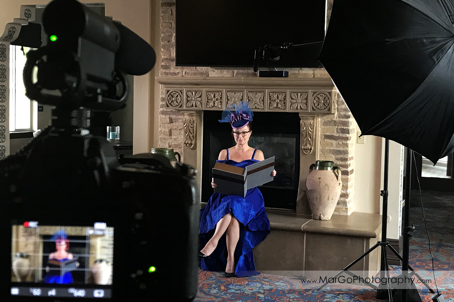 behind the scenes of indoor filming woman speaker in blue dress and hat sitting in fornt of fireplace