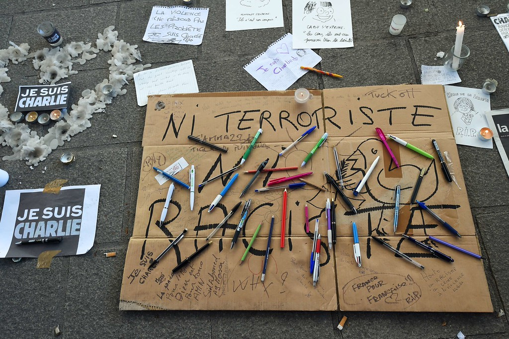 . Pens are placed on cardboard reading \'\'Neither terrorist nor racist\'\'  at the old harbour in Marseille on January 8, 2015 after people observed a minute of silence for the victims of an attack by armed gunmen on the offices of French satirical newspaper Charlie Hebdo in Paris on January 7 which left 12 people dead. A stunned and outraged France was in mourning yesterday, as security forces desperately hunted two brothers suspected of gunning down 12 people in an Islamist attack on a satirical weekly. AFP PHOTO / ANNE-CHRISTINE POUJOULAT/AFP/Getty Images
