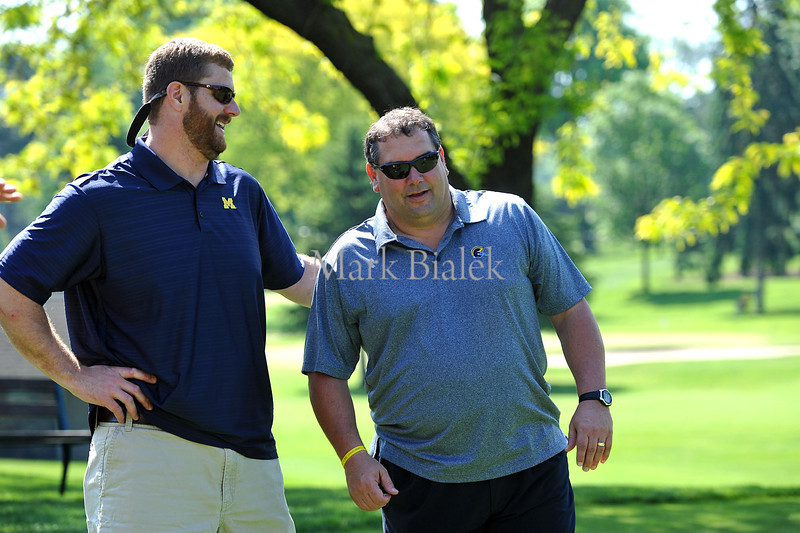 Detroit Lions offensive tackle Jeff Backus talks to University of Michigan second-year head coach Brady Hoke during the Griese Hutchinson Woodson Champion for Children's Hearts charity golf event at the U-M golf course in Ann Arbor on May 20, 2012.  Money was raised for Mott Children's Hospital.  MARK BIALEK/Special to the Free Press