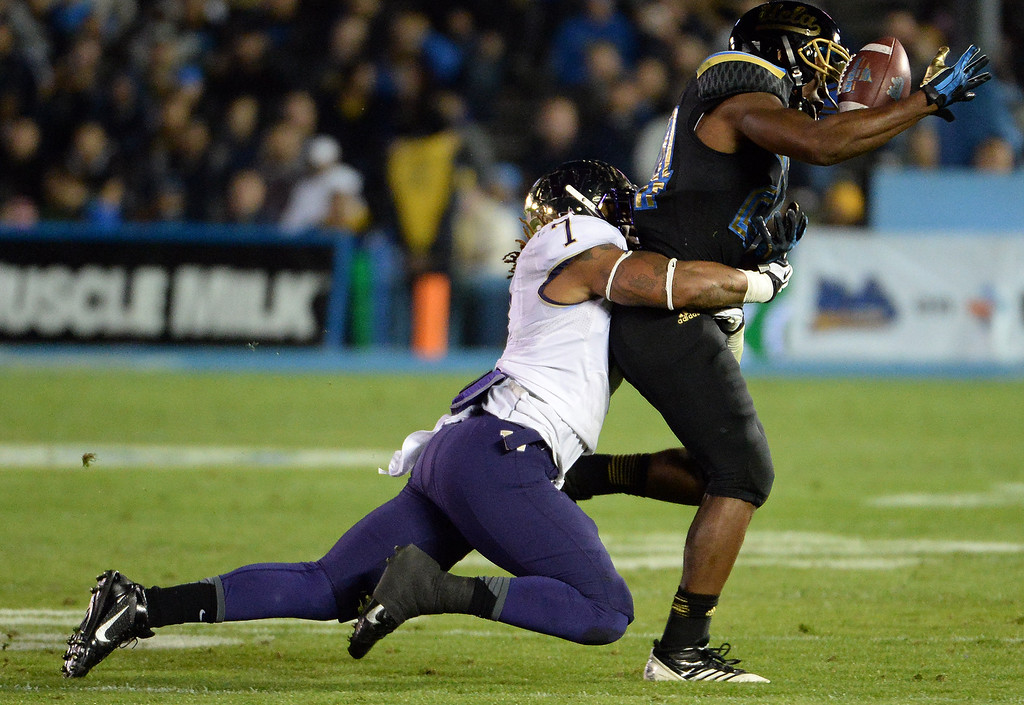 . Washington Huskies\'s Sean Parker (1) tackles UCLA Bruins running back Paul Perkins (24) as he drops the pass during the first half of their college football game in the Rose Bowl in Pasadena, Calif., on Friday, Nov. 15, 2013.  UCLA won 41-31.   (Keith Birmingham Pasadena Star-News)