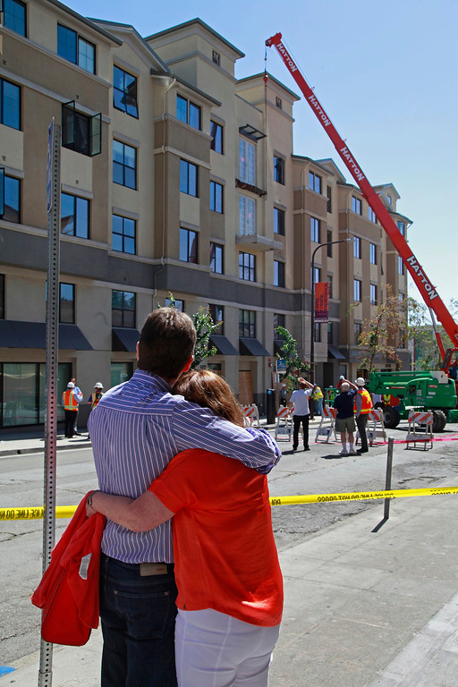 . Friends of one of the victims, who did not want to talk to the media, hug as they watch workers prepare the lower balcony for removal outside the Library Gardens apartments in Berkeley, Calif. on Wednesday, June 17, 2015. Six people died and seven others were seriously injured when the balcony collapsed early Tuesday morning during a birthday party. (Laura A. Oda/Bay Area News Group)