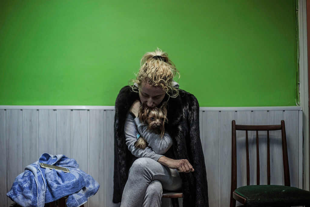 . A Ukrainian woman embraces her dog in a shelter during the heaviest exchange of artillery fire in the last few days, at Voroshilovsky area, center of Donetsk, Ukraine. Sunday, Jan. 18, 2015. The separatist stronghold, Donetsk, was shaken by intense outgoing and incoming artillery fire as a bitter battle raged for control over the city\'s airport. Streets in the city, which was home to 1 million people before unrest erupted in spring, were completely deserted and the windows of apartments in the center rattled from incessant rocket and mortar fire. (AP Photo/Manu Brabo)