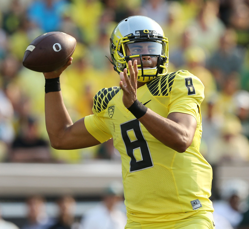 . Oregon\'s Marcus Mariota passes down field against  Michigan State during the 2nd quarter of their college football game in Eugene, Ore. Saturday Sept. 6, 2014. (AP Photo/Chris Pietsch)