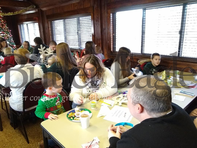 Mason Messina, 3, works on a craft with his mother, Anna, and father, Ken, at Breakfast with Santa on Saturday, Dec. 7, 2019, at the Butler Township Park Building. The family recently moved to Center Township from North Dakota. Donna Sybert/Butler Eagle